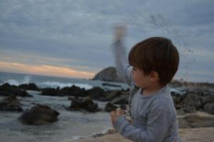 boy throwing rocks on cabo del sol beach near sunset